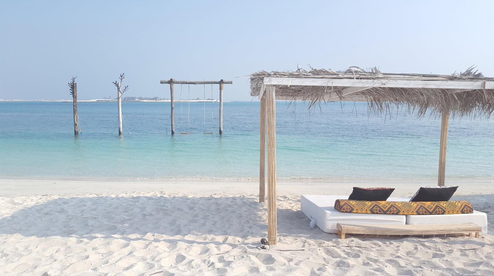 Balancoire dans la mer et lit sur la plage
