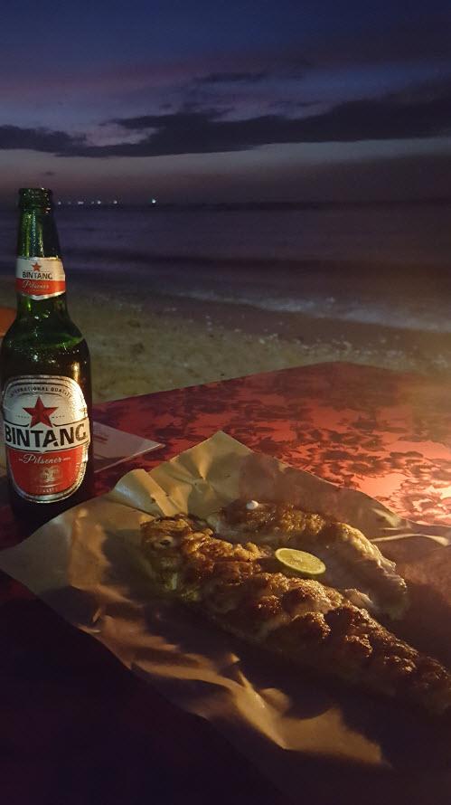 Poisson frais grille au barbecue sur la plage